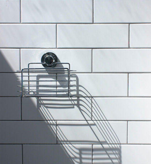 closeup of a shower rack on a tile wall