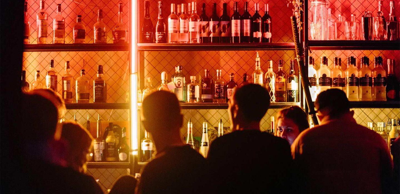 guests around bar under dim neon lighting