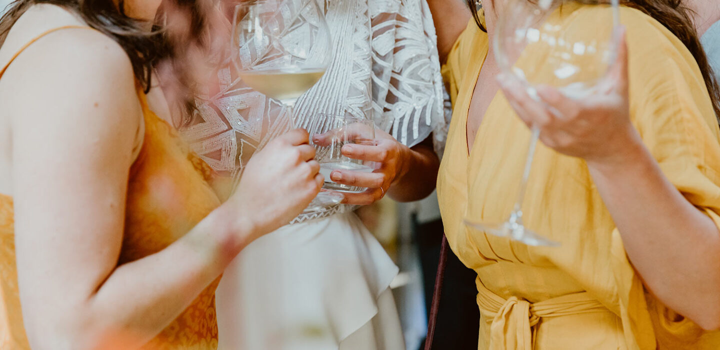 bride and two friends stand together holding glasses of white wine