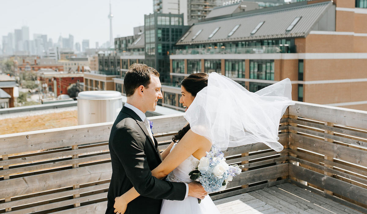 bride and groom smile while holding each other on rooftop