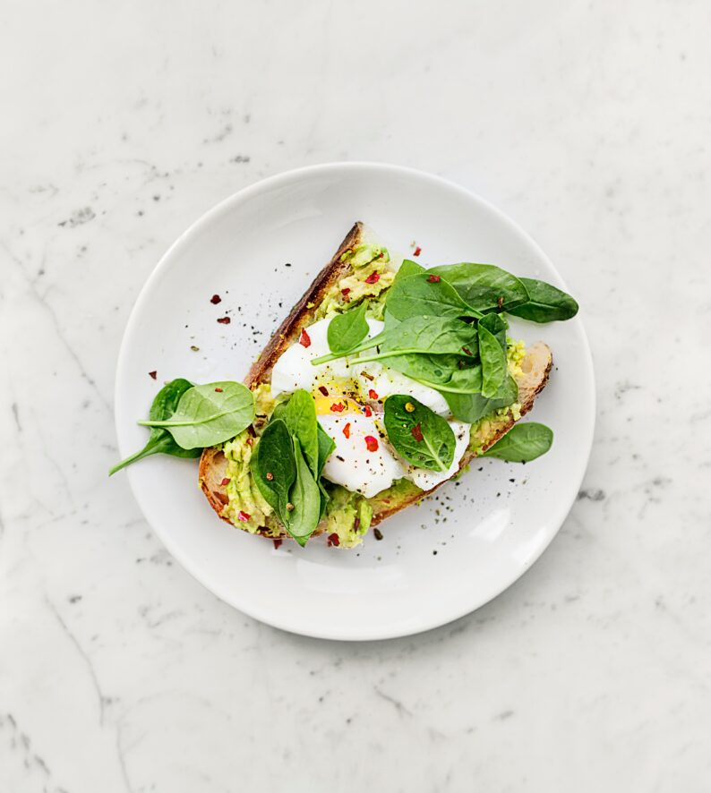 overhead view of a piece of avocado toast with an egg and spinach on top