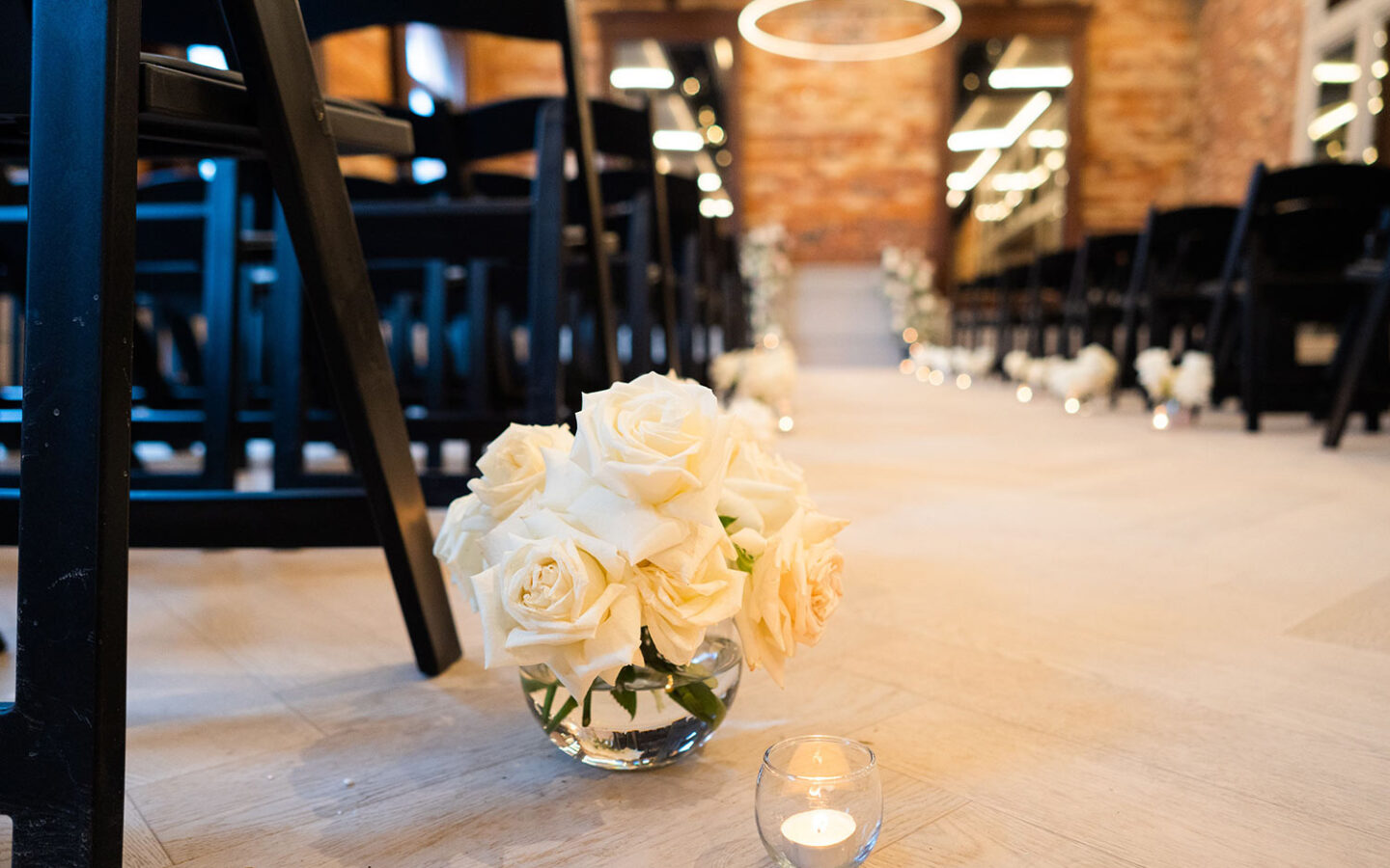 white roses in a clear bowl on the floor of a wedding reception aisle