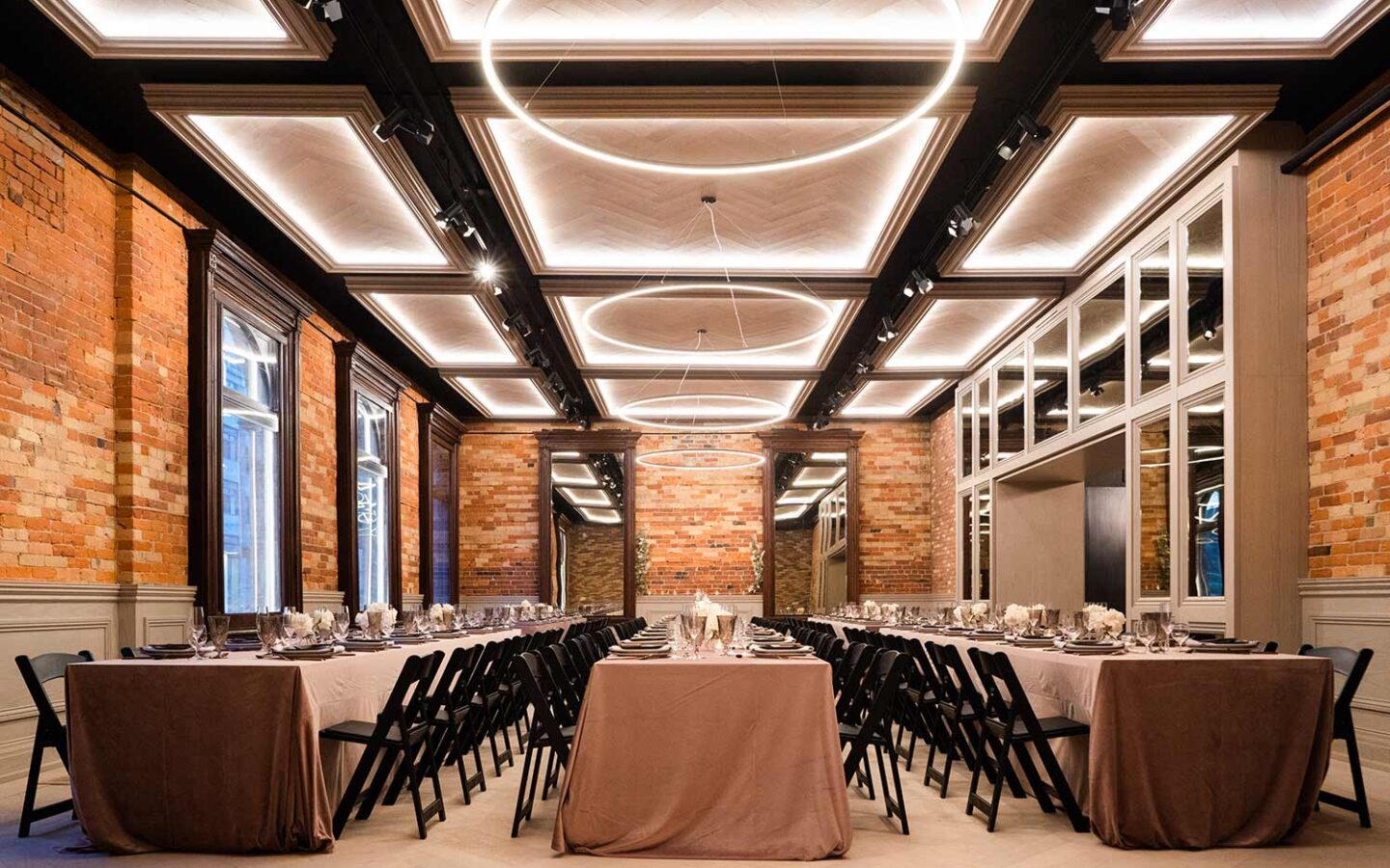 wedding venue with long rectangular tables and high brick walls with approximately 150 seats